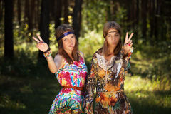两个愉快的年轻时尚女孩在夏天森林里 免版税库存照片