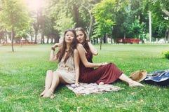 两个愉快的boho别致的时髦的女朋友在公园去野餐 库存图片
