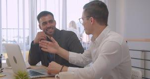 两个成人成功的商人画象研究膝上型计算机和有讨论在办公室户内 股票视频