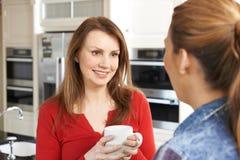 两个成熟女性朋友一起谈话在厨房里 库存图片