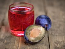 两个成熟李子和一杯在一张木土气桌上的新鲜的自创李子开胃酒 库存照片