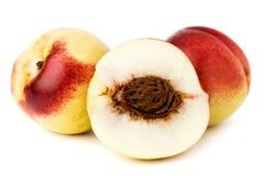 两个成熟油桃和一半在白色背景 库存照片