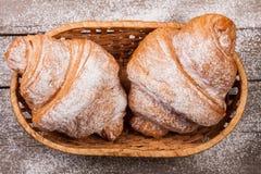 两个新月形面包洒与在一个柳条筐的搽粉的糖在老木板顶视图 库存照片