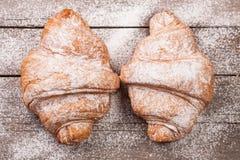 两个新月形面包洒与在老木板顶视图的搽粉的糖 库存照片
