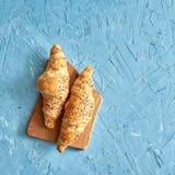 两个新鲜的新月形面包,在蓝色背景的木切板 顶视图 免版税库存照片