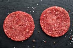 两个新鲜的未加工的头等黑安格斯牛肉汉堡小馅饼 免版税库存照片