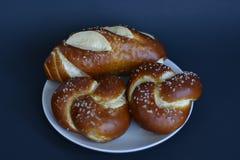 两个新鲜的被烘烤的椒盐脆饼小圆面包和一椒盐脆饼次级卷在一块白色板材有黑背景 库存图片