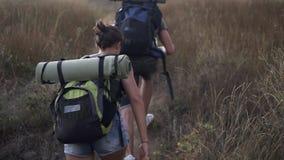 两个旅客大角度英尺长度-男人和妇女攀登与游人背包的小山在后面 早晨 影视素材