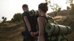 两个旅客-男人和妇女有巨大的背包的步行 走由草小山,当结合在一起时使手 晒裂 股票视频