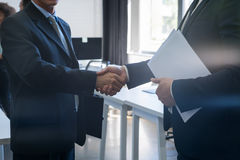 两个无法认出的商人震动手协议Coworking中心企业队工友 免版税库存照片