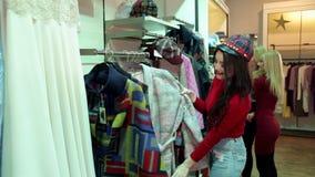 两个时兴的白肤金发的女孩选择在一家大服装店的衣裳 影视素材
