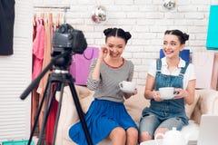 两个时尚博客作者女孩喝与marshmellows的茶对照相机 免版税库存照片