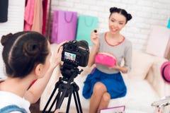 两个时尚博客作者女孩阻止与一个女孩的五颜六色的首饰在照相机后 免版税库存照片