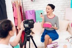 两个时尚博客作者女孩阻止与一个女孩的五颜六色的首饰在照相机后 免版税库存图片