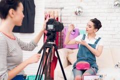 两个时尚博客作者女孩阻止与一个女孩的五颜六色的首饰在照相机后 库存图片
