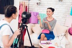 两个时尚博客作者女孩阻止与一个女孩的五颜六色的首饰在照相机后 图库摄影