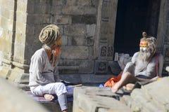 两个明智的信奉瑜伽者的交谈Pashupatinath寺庙的,尼泊尔,加德满都, 2017年12月 图库摄影