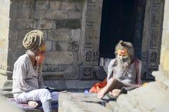 两个明智的信奉瑜伽者的交谈Pashupatinath寺庙的,尼泊尔,加德满都, 2017年12月 免版税库存照片