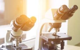 两个显微镜在实验室里,特写镜头,阳光站立 库存照片