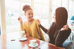 两个最好的朋友在咖啡馆坐并且一起花费好时间 女孩喝着他们一些的拿铁和享用 免版税库存图片