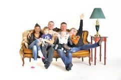 两个有孩子的傻瓜坐沙发的年轻家庭戏剧 免版税库存照片