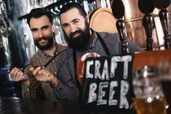 两个有胡子的人在手抽烟管子举行,站立近的标志用题字工艺啤酒 免版税库存照片