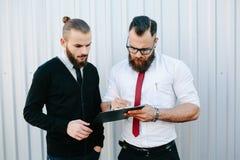 两个有胡子的商人签署的文件 免版税库存图片