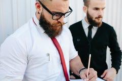 两个有胡子的商人签署的文件 库存图片