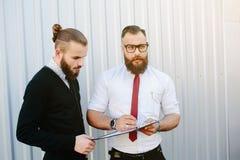 两个有胡子的商人签署的文件 库存照片