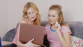 两个朋友使购买网上 少妇与膝上型计算机坐长沙发,在手上拿着一张信用卡 股票录像