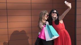 两个朋友做与滑稽的面孔的一selfie 女孩晴朗的画象  太阳镜的美丽的女孩有购物袋的 股票录像