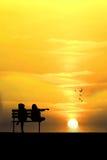 两个朋友剪影坐木长凳在海滩附近 库存图片