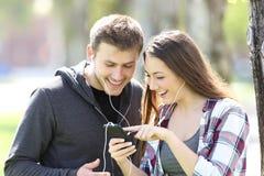 两个朋友听的音乐和选择歌曲 免版税库存图片
