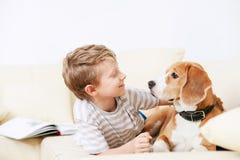 两个朋友-一起说谎在沙发的男孩和狗 库存图片