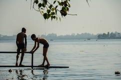 两个未认出的未知的可怜的贫民窟男孩,佩带的短裤,使用在Versova海滩附近,孟买,马哈拉施特拉,印度 免版税库存图片
