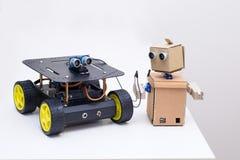 两个机器人在家在一张白色桌上 免版税库存图片