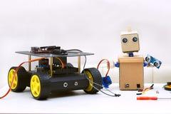 两个机器人在桌上,其次是装配的t零件 免版税库存照片