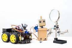 两个机器人在白色背景的一张桌上站立 免版税库存照片