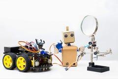 两个机器人在白色背景的一张桌上站立 库存图片