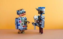 两个机器人通信,机器学习概念 机器人字符,可调扳手扳手 黄色墙壁,棕色 免版税库存照片