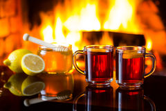 两个杯子与壁炉的热的饮料在背景 免版税图库摄影