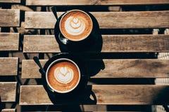 两个杯子与拿铁艺术的热奶咖啡 免版税库存图片