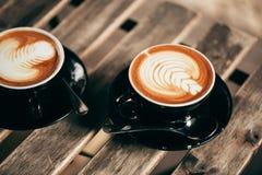 两个杯子与拿铁艺术的热奶咖啡 图库摄影
