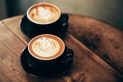 两个杯子与拿铁艺术的热奶咖啡 库存照片
