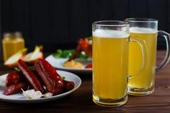 两个杯子与有壳的烤鸡翼和var的储藏啤酒 库存图片