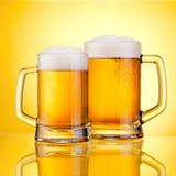 两个杯子与泡沫盖帽的新鲜的啤酒,在黄色 库存照片