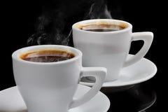 两个杯子与蒸汽的热的咖啡在黑背景 免版税库存图片