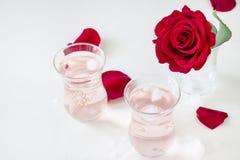 两个杯子刷新与冰块的奉承话柠檬水和罗斯在玻璃和瓣开花在白色背景 选择聚焦 免版税库存图片