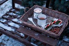 两个杯子在一个柳条筐的热的可可粉在一张木桌上 免版税库存照片