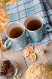两个杯子在一块亚麻制蓝色餐巾的热的茶 干八仙花属,柠檬,栗子,桂香 免版税库存照片